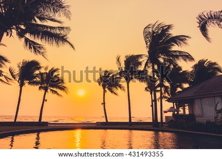 Silhouette palm tree on the beach and sea around beautiful luxury swimming pool in sunset - Vintage Filter and Boost up color Processing