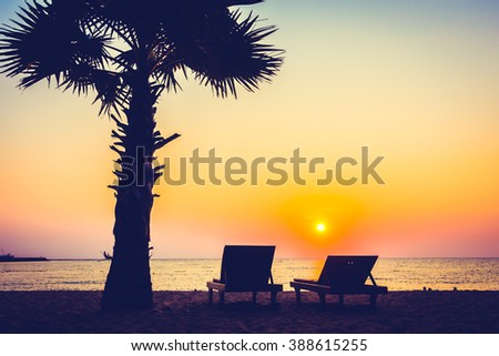 Silhouette palm tree on the beach with empty chair at sunset times - Vintage Filter and Boost up color Processing - stock photo