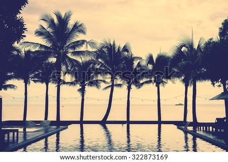 Silhouette palm tree on the beach with swimming pool in hotel resort - vintage filter effect