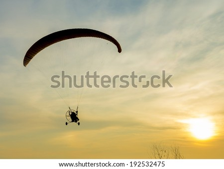 Silhouette paramotor in sunset. - stock photo
