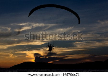 Silhouette paramotor / paraglider flying  on the sky with seaview - stock photo
