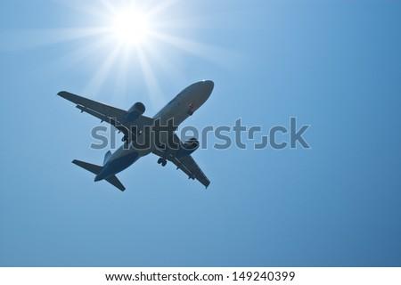 Silhouette passenger airplane against bright sun - stock photo
