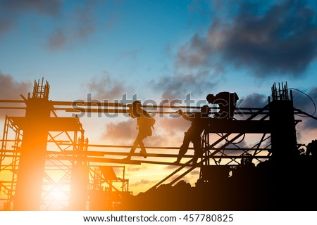 Silhouette People heavy industrial sector construction worker, plans to comply with the planning engineers on the scaffolding over blurred background pastel. Heavy industry and safety at work concept. - stock photo