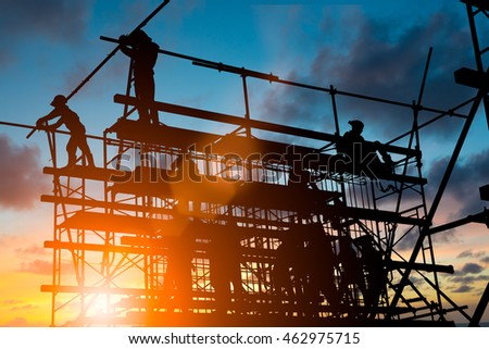 Silhouette People heavy industrial sector construction worker, plans to comply with the planning engineers on the scaffolding over blurred background pastel. Heavy industry and safety at work concept.