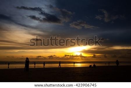 Silhouette people man a woman on the sunset background / Sunset on the tropical beach Seminyak / Bali, Indonesia - stock photo