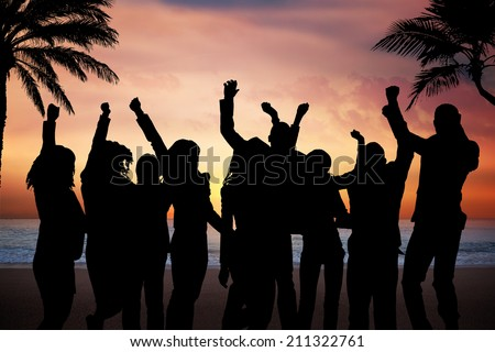 Silhouette people partying on beach at sunset - stock photo