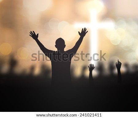 Silhouette people raising hands over blurred the cross on beautiful golden autumn sunset background. Worship, Forgiveness, Mercy, Humble, Repentance, Reconcile, Adoration, Glorify, Redeemer concept. - stock photo