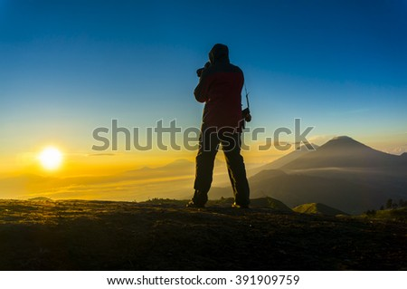 silhouette photographer action during sunrise on prau mount central java indonesia - stock photo