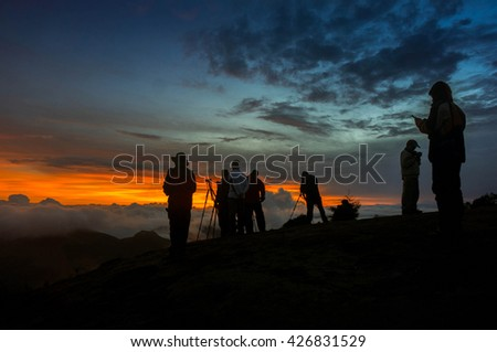silhouette photographer during sunset and fog - stock photo