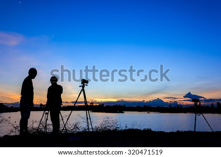 Silhouette photographers with sunset background - stock photo