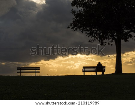 Silhouette portrait of a lonely anonymous man sitting on a bench as dark clouds above him roll, with the sun beginning to set behind - stock photo