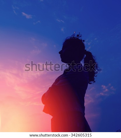Silhouette portrait of young serious woman. Silhouette of a young woman relaxing on a beautiful sunset. Happy woman enjoying nature sunset. Freedom, happiness, enjoyment, concept of beautiful girl.  - stock photo