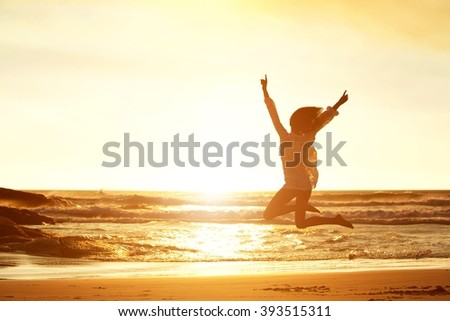 Silhouette portrait of young woman jumping for joy at beach during sunset  - stock photo