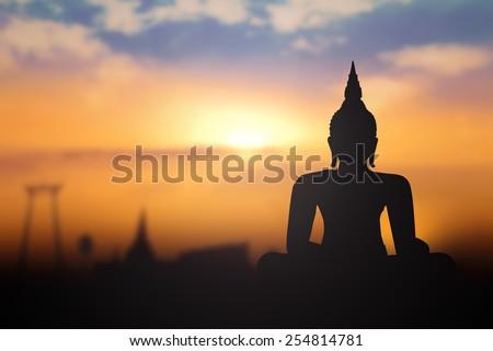Silhouette public big white Buddha, over golden light sunset in Thailand background. Travel, End of Buddhist Lent, Theravada New Year, Vesak Day, Jayanti, International concept. - stock photo