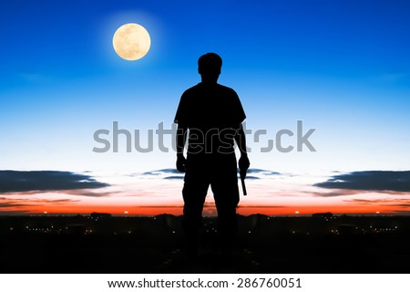 silhouette rear of man standing hand hold holding gun revolvers on sunrise and full moon on the sky in the city background - stock photo