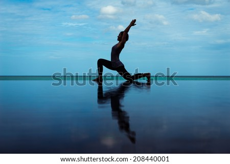 silhouette Reflection of low lunge in Yoga pose with blue sky - stock photo