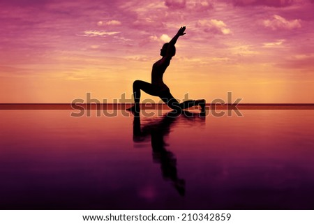 silhouette Reflection of low lunge in Yoga pose with sunset background - stock photo