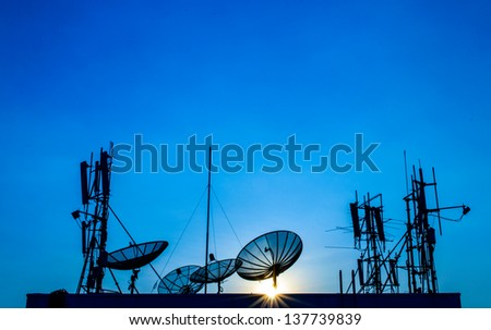 Silhouette Satellite Dish and Communication Tower on Sunset Time. - stock photo