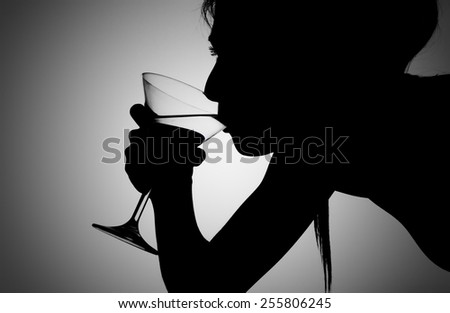 Silhouette shot of a female drinking a martini. - stock photo