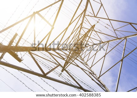 Silhouette shot of electricity pylons, natural golden sunlight at background.