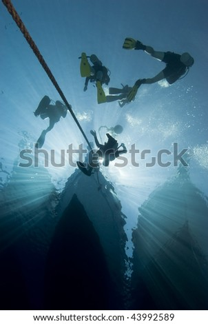 Silhouette shot of scuba divers at the bow of a dive boat. Red Sea, Egypt. - stock photo