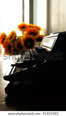 Silhouette shot of vintage type writer with rim light on the desk next to sun flowers. Text space is available at the bottom. - stock photo