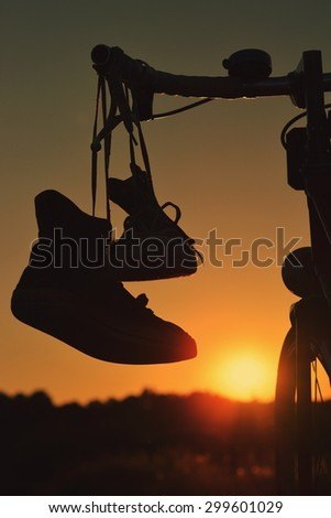Silhouette sneakers hung on bike - stock photo