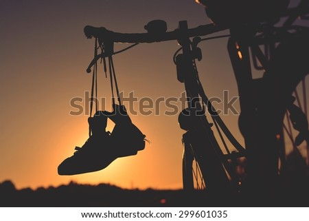 Silhouette sneakers hung on bike with retro effect