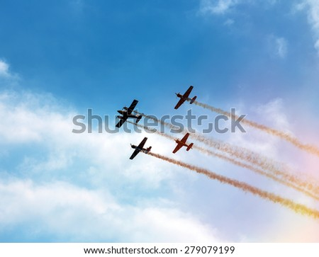 Silhouette sport aircraft with propellers, performing tricks with a smokescreen against the blue sky in the air show performance - stock photo