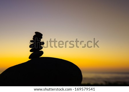 Silhouette stack of small rocks on a large rock at sunset