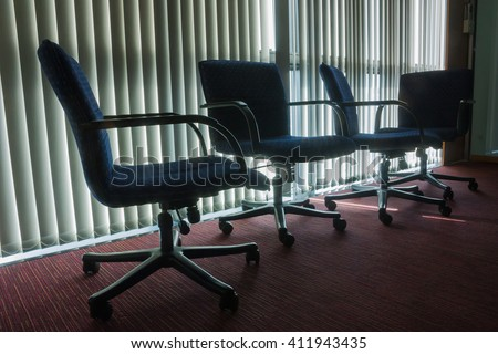Silhouette Styled And Dark Tone Of Four Empty Chairs In Office With Blind Background