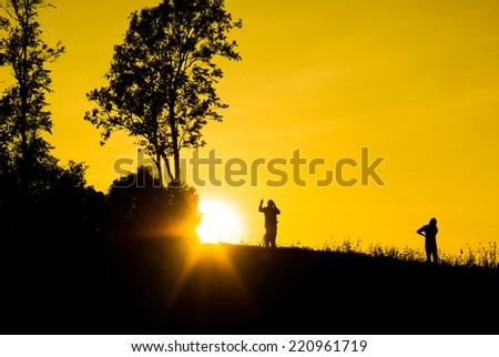 Silhouette sunrises and the man on mountain at Thailand.