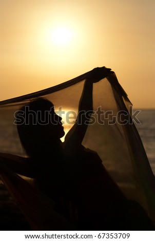 Silhouette take of an oriental dancer  at sunrise - stock photo