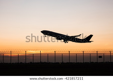 Silhouette takeoff plane from the airport while sunset - stock photo