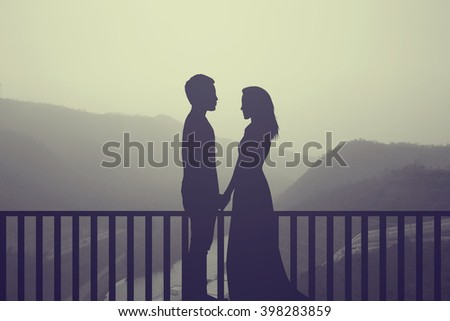 silhouette teenager/adult lovers couple over natural background at the beach and mountain:black shadow love people touch hand:valentines concept:affection/wedding/anniversary:vintage filter effect - stock photo