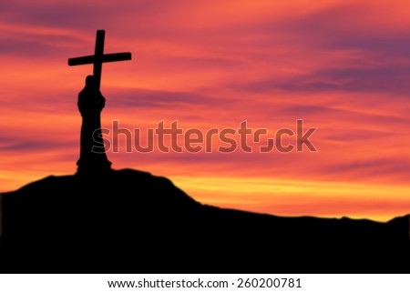 Silhouette the cross over blurred sunset background - stock photo