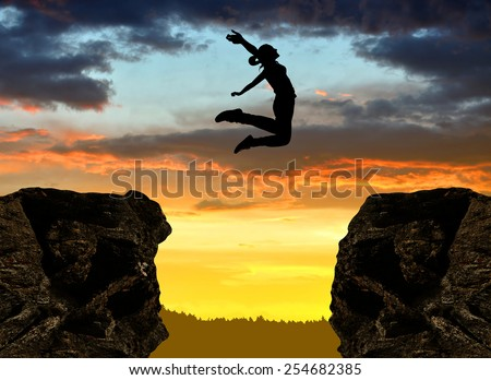 Silhouette the girl jumping over the gap at sunset - stock photo