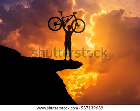 Silhouette the man in action lifting mountain bicycle above his head stand on top of the rock cliff with sunset twilight background.