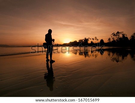 Silhouette the photographer see the camera screen view golden sunset - stock photo