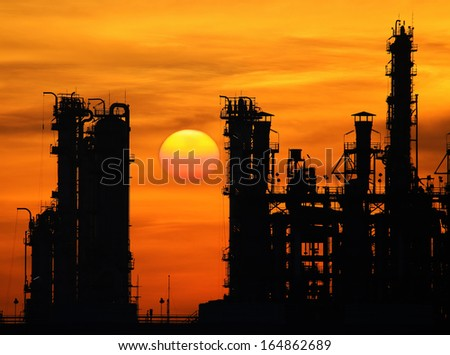 silhouette tower of oil refinery at sunrise - stock photo