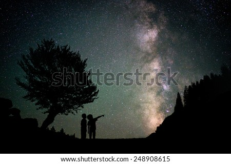 Silhouette two little boys with Milky Way and beautiful night sky full of stars in background - stock photo