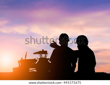 silhouette two men to operate heavy machinery plowed soil in preparation for planting crops. The main industry of the world. concept food crop. concept to save the world. - stock photo