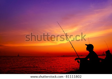 silhouette two people are fishing - stock photo