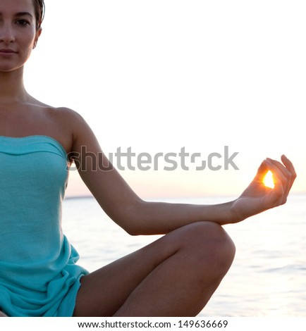 Silhouette view of a healthy young woman sitting in a yoga position meditating, with the sun filtering through her fingers in a circle during sunset on a tranquil beach. - stock photo