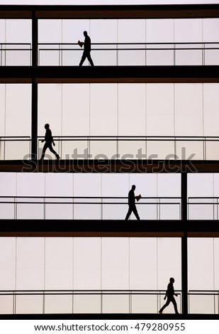Silhouette view of businessmen in a modern office building interior with panoramic windows.