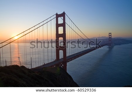 Silhouette view of Golden Gate Bridge at sunrise
