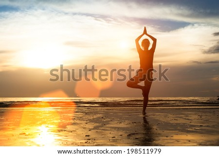Silhouette woman exercise on the beach at sunset. - stock photo