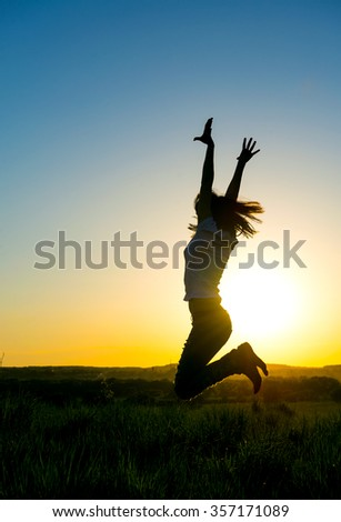 Silhouette woman jumping in front of a beautiful sunset.  Sensual girl with sun rising behind her. - stock photo