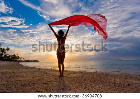 silhouette woman on tropical beach with scarlet red sarong blowing in tropical wind