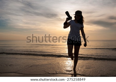 Silhouette woman photographer walking on beach with hand holding camera at sunrise. - stock photo